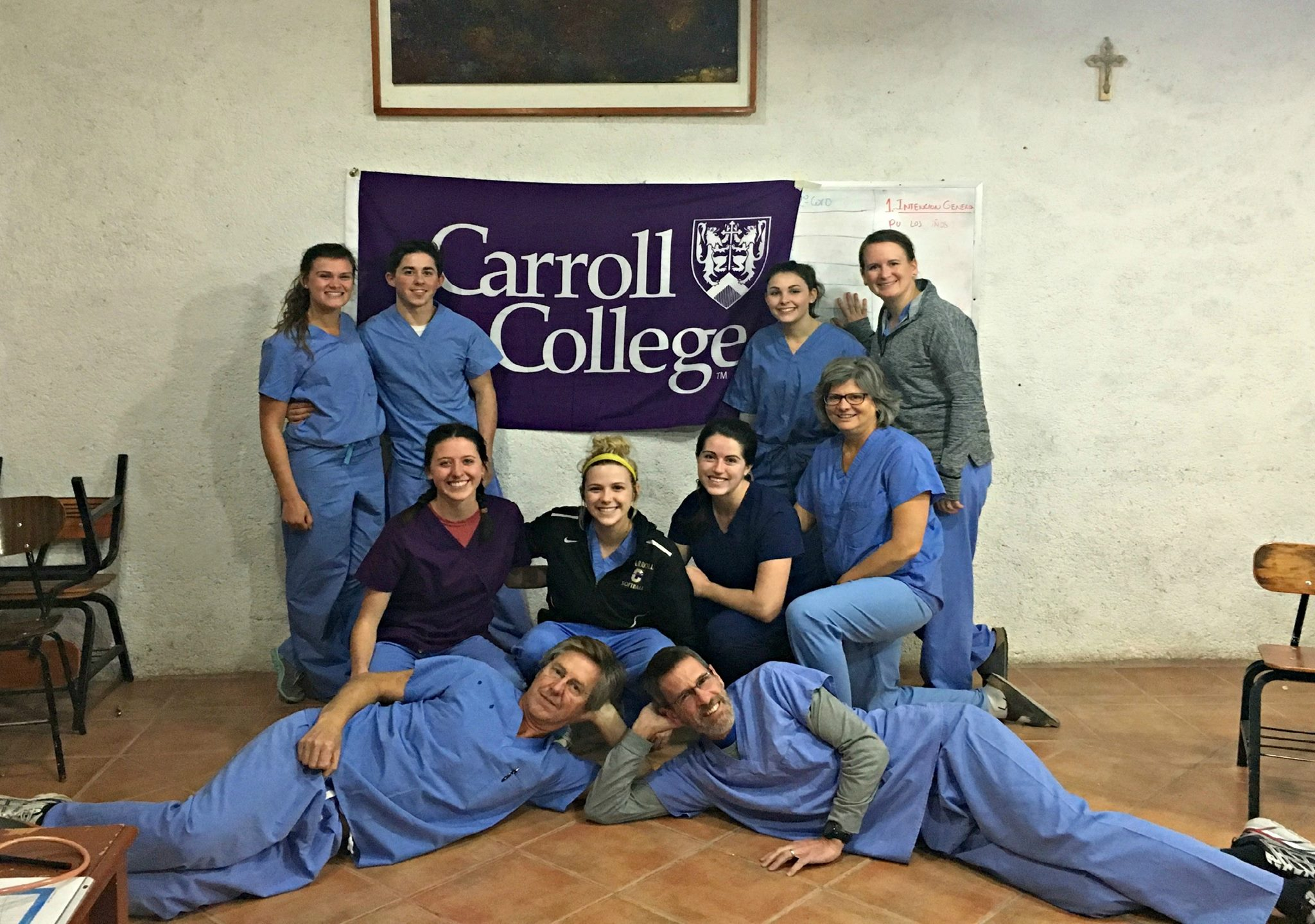 Carroll College Nursing Students pose next to a Carroll College Flag