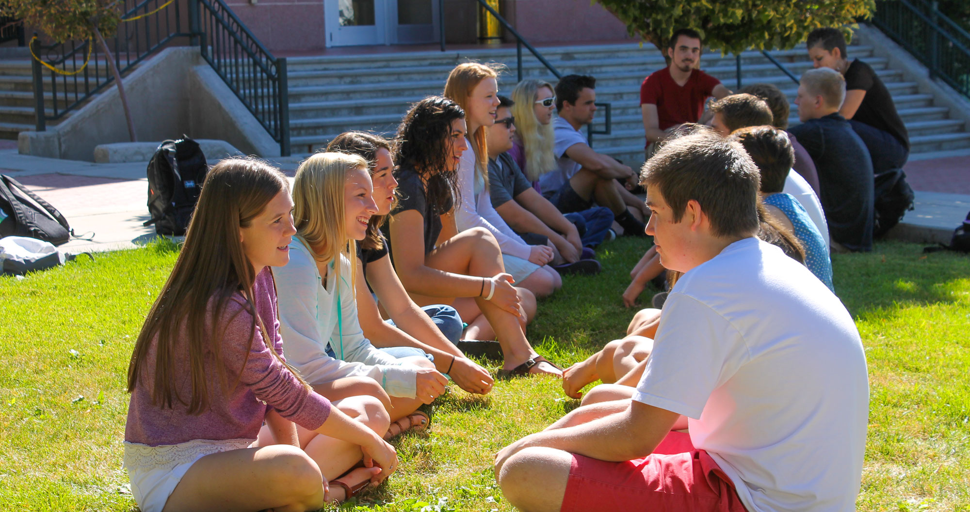 Image of students sitting in grass on campus