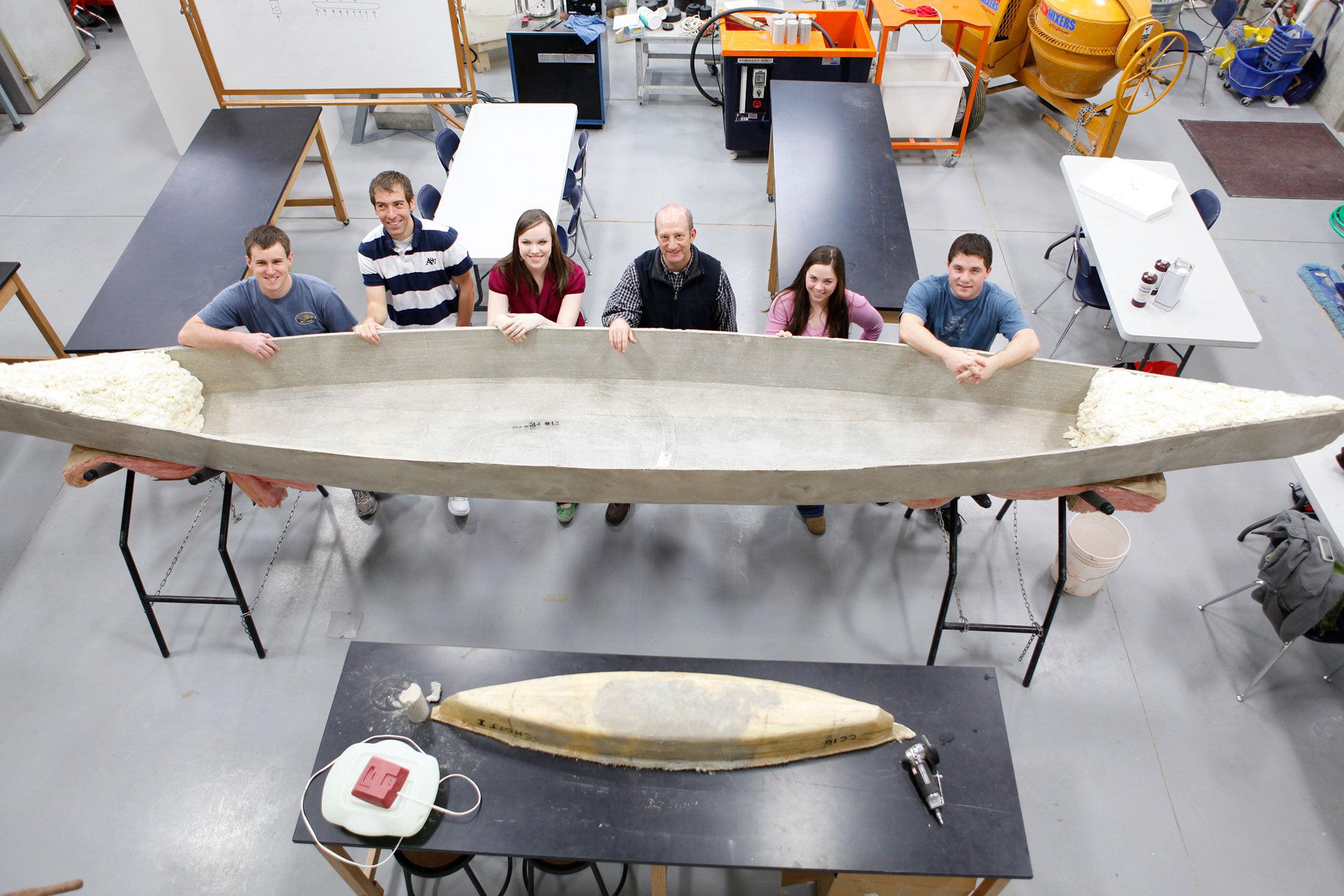 Image of students displaying a canoe made of cement