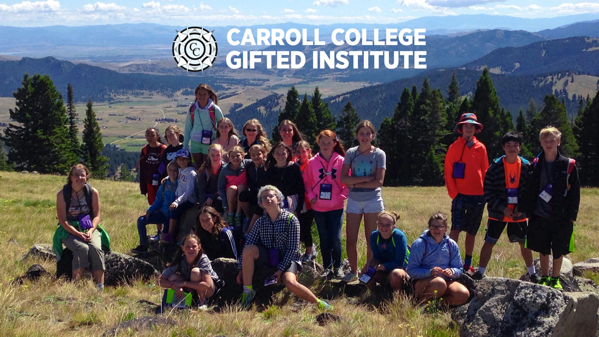 Gifted Institute - Students laying on the grass looking up at the camera and smiling