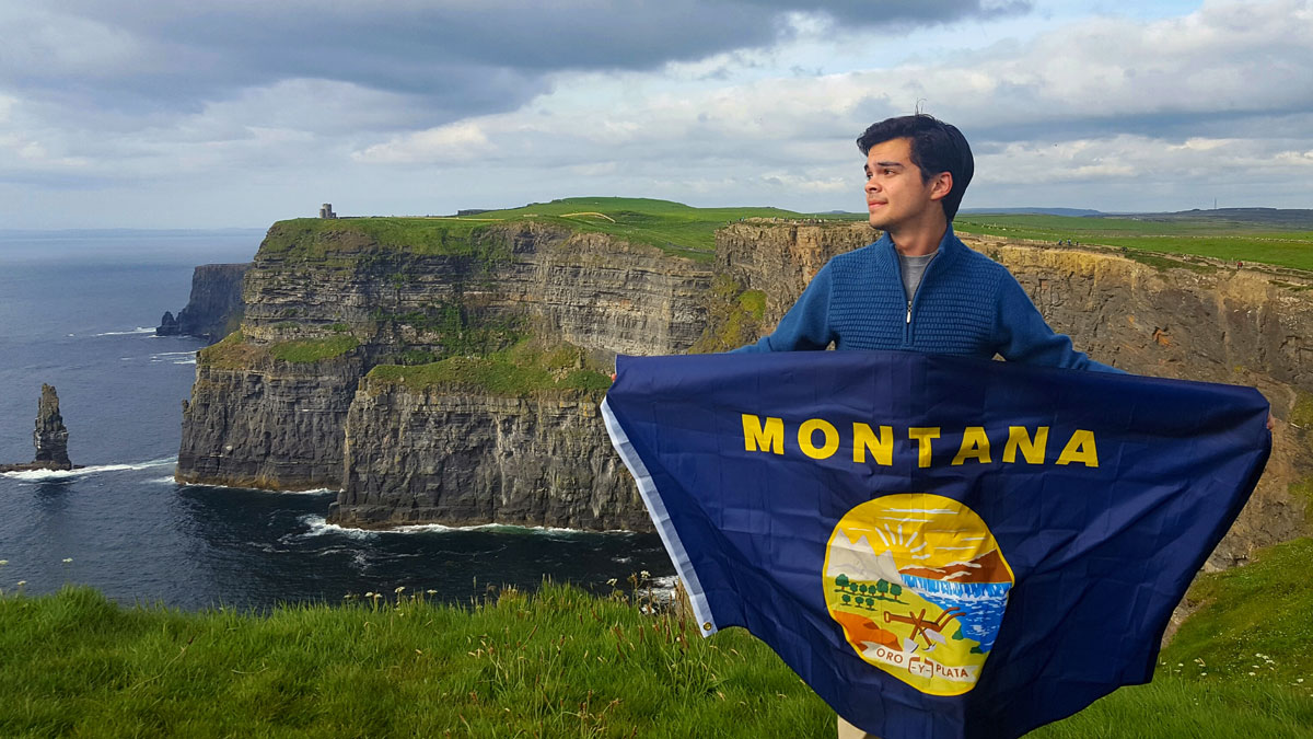 Luke on the Cliffs of Mohr with Montana flag