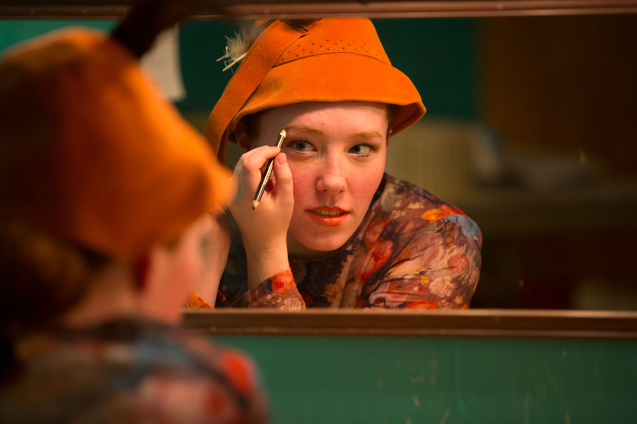 Carroll College Theatre student applying make-up in a mirror