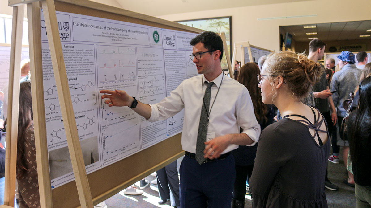 Photo of a student showing off his research at the Carroll College Student Undergraduate Research Festival.