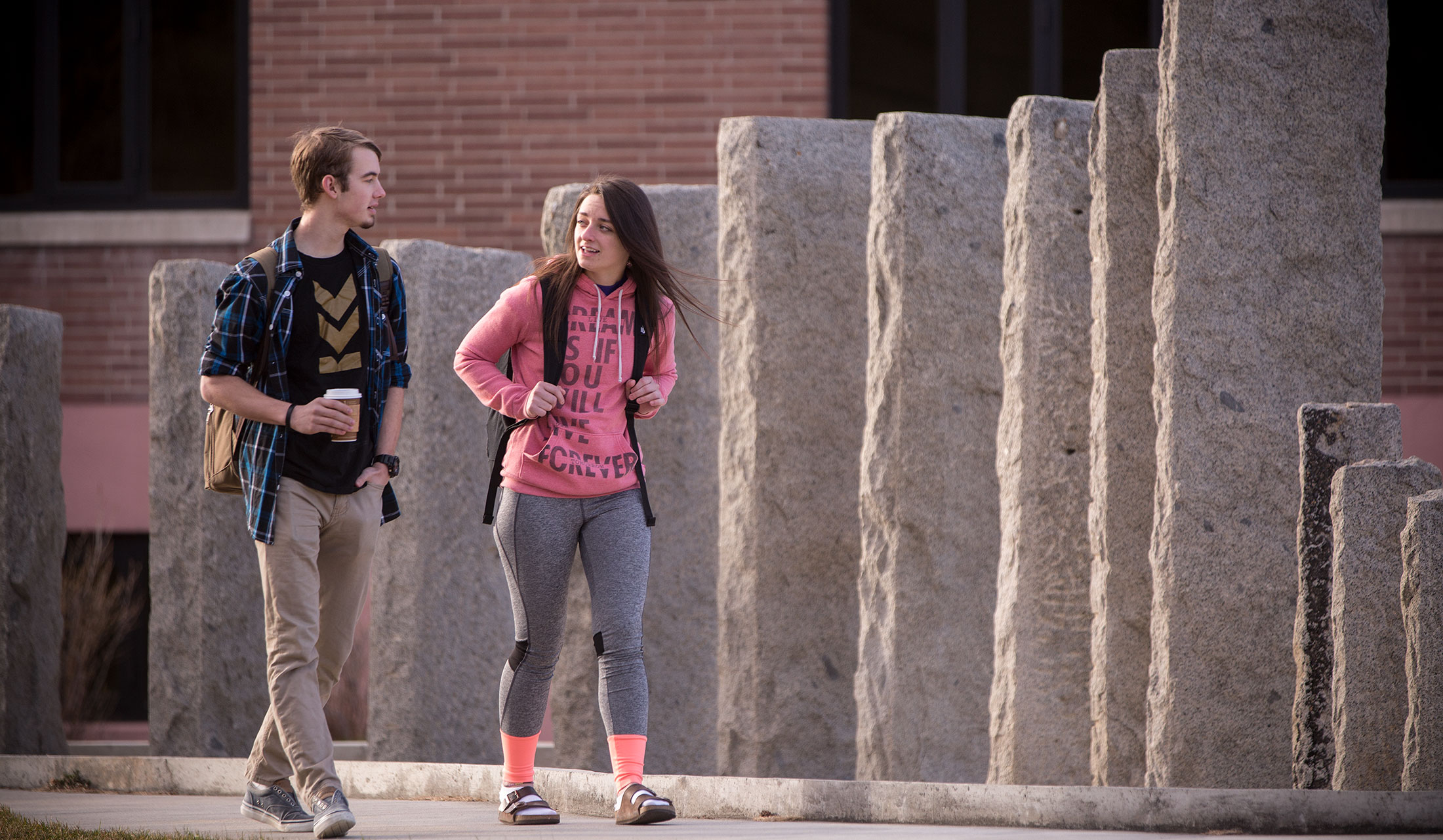 Two students walking by the Sladich Fountain