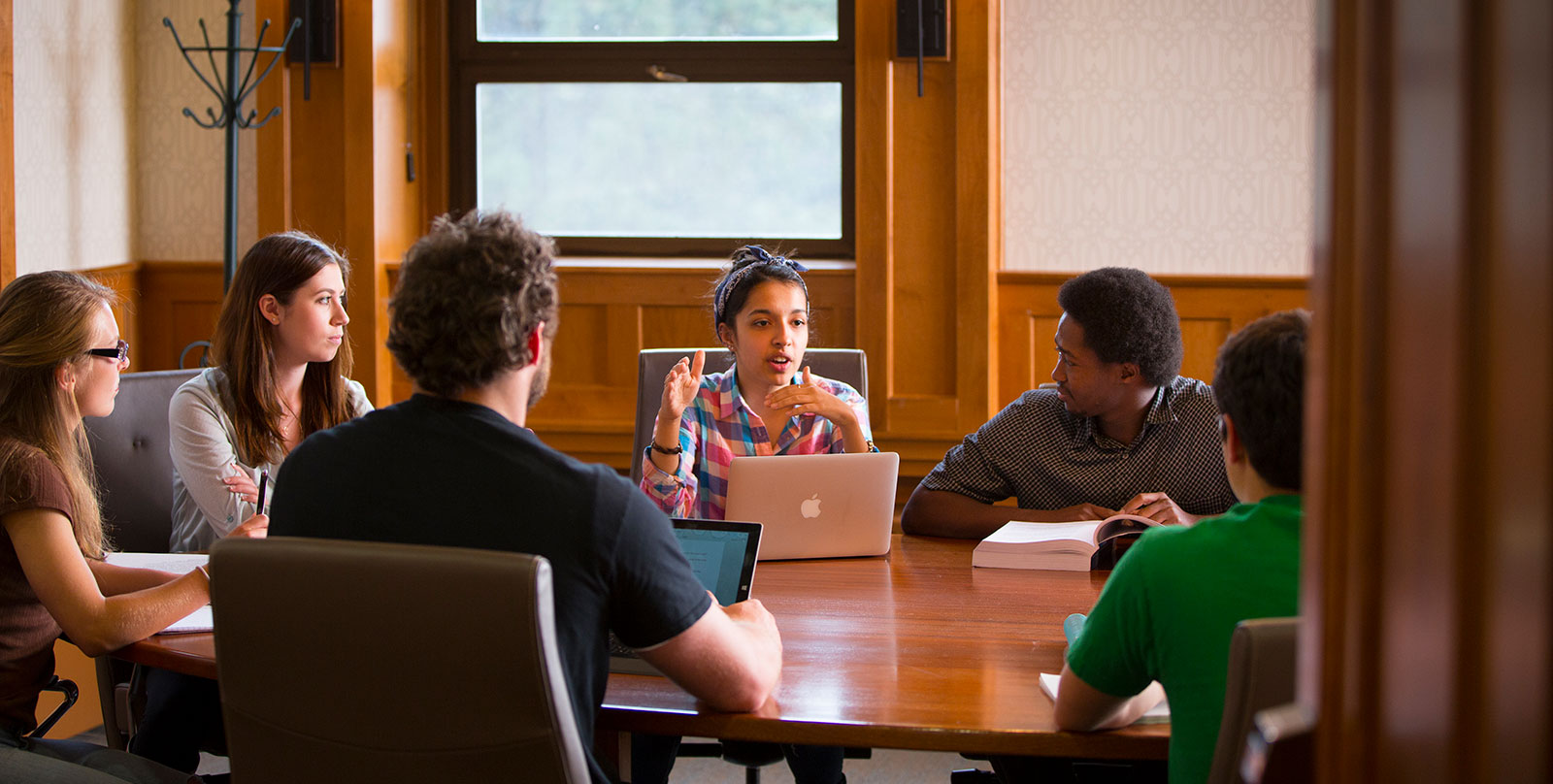 Image of Carroll College Students sit around Conference Table