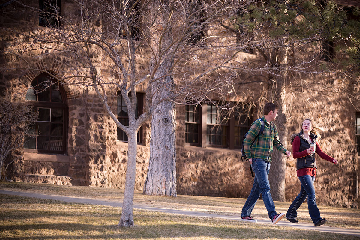 Two students walking on campus on a fall day