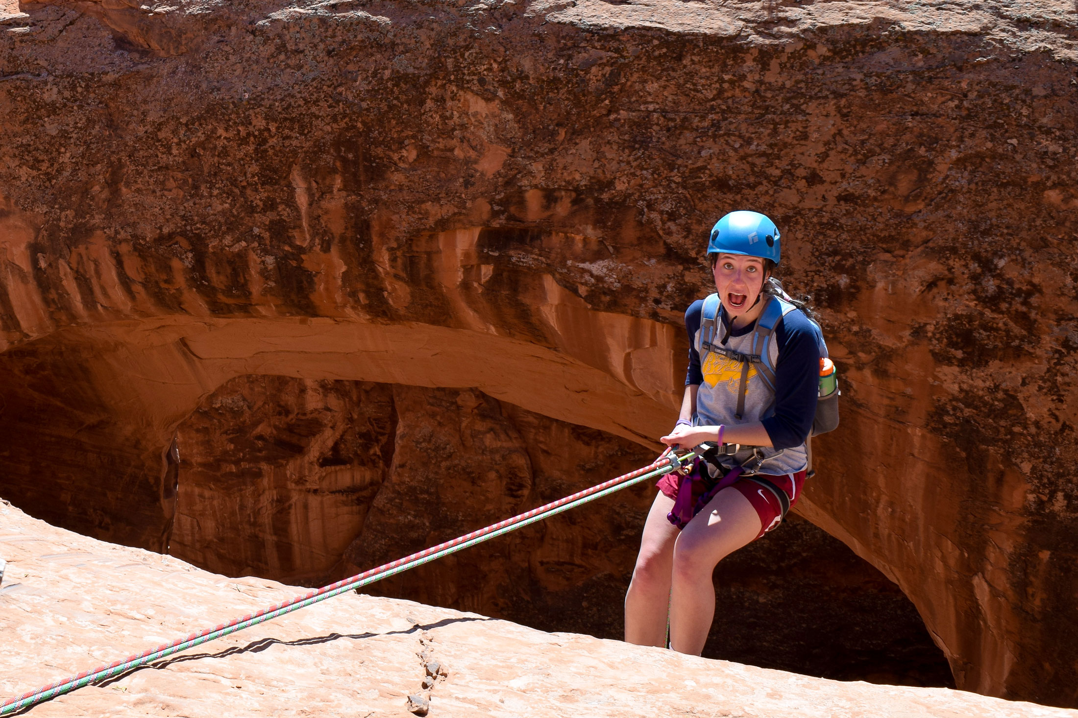 Elle Barta repelling down a large rock in the desert