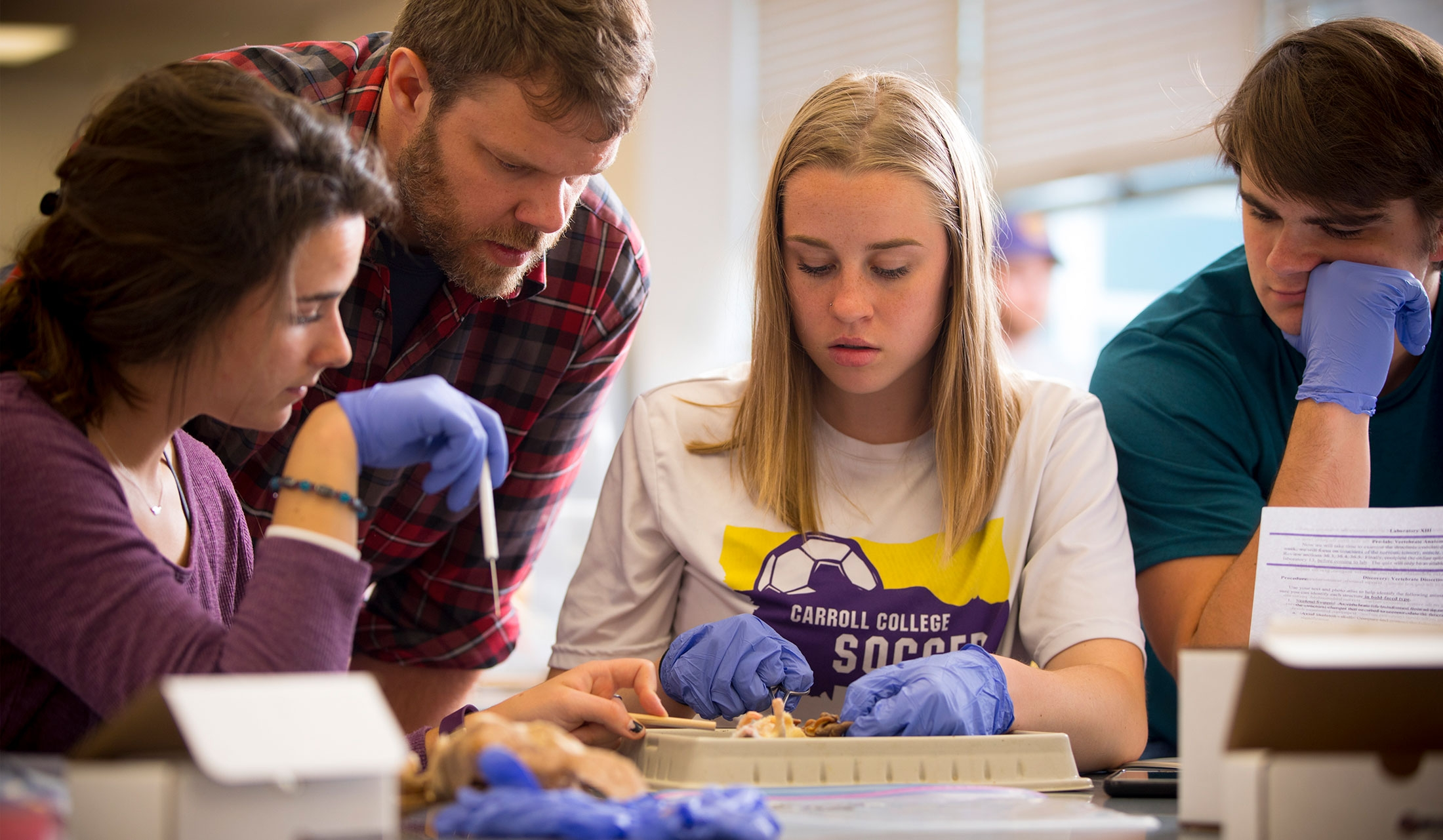 Photo of Dr. Travis Almquist and students in biology lab