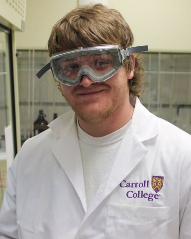Portrait of Dustin Williams wearing safety goggles and a lab coat