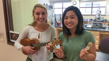 Lauren Rhoda and Victoria Kong holding instruments and brushes