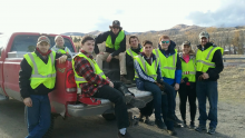 ASCE students sitting on the back of a truck getting ready to clean up interstate 15