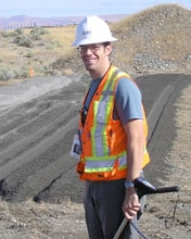 Andrew Powers working in the field wearing an orange safety vest