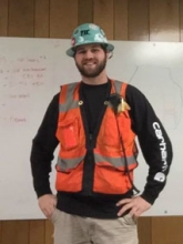 Snapshot of Tyson Cooper in a hard hat and orange vest