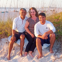 Portrait of Sandy '84 and Raj Lall with son on a sandy beach