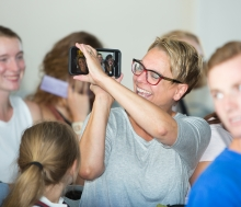 Kim Johnson taking video or a photo with her phone